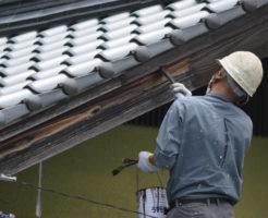 破風板の塗装をする職人